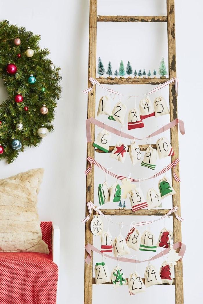 DIY Leiter Adventskalender, nummerierte Säckchen voll mit kleinen Geschenken, Weihnachtskranz aus Tannenzweigen mit bunten Christbaumkugeln