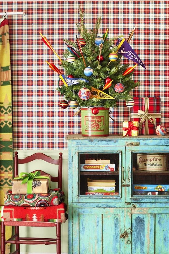 Kleiner Weihnachtsbaum in Eimer, geschmückt mit bunten Christbaumkugeln, vintage Möbel, karierte Tapete