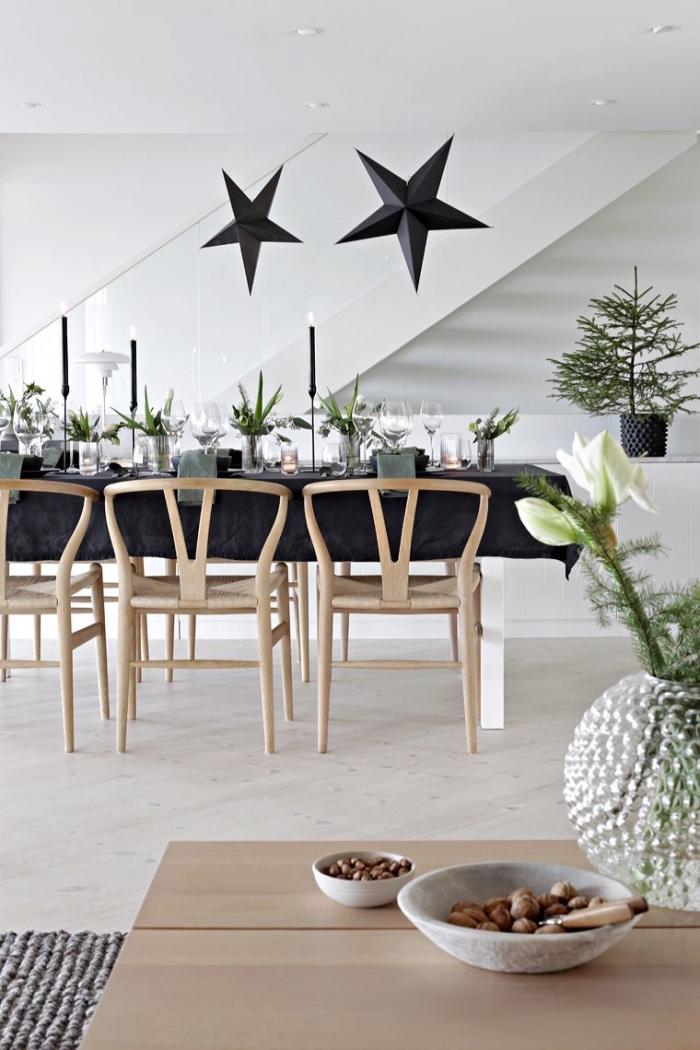 weihanchtliche tischdeko in schwarz, große hängende sterne, vase mit blumen, lange kerzen