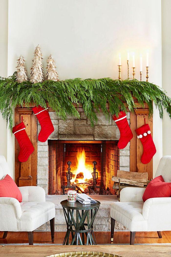 Kamin weihnachtlich dekorieren, grüne Zweige, vier rote Weihnachtsstrümpfe, Kerzen und kleine Weihnachtsbäume