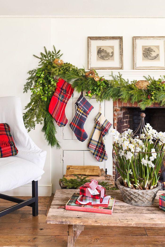 Kamin weihnachtlich dekorieren, Tannengirlande und drei karierte Weihnachtsstrümpfe