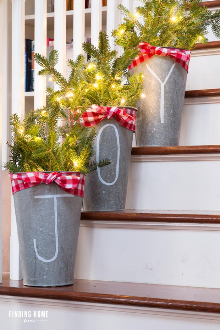 Weihnachtsdeko im Garten, Tannenzweige geschmückt mit Lichtern in Eimern mit Aufschrift Joy