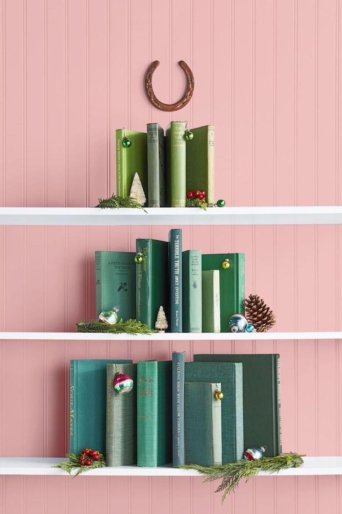 Weihnachtsbaum aus Büchern mit grünen Buchdeckeln auf weißen Regalen, Hufeisen für Spitze