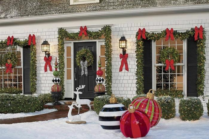 weihnachtsdeko fenster basteln weihnachten vor dem haus deko grüne weihnachtskränze große kugeln hirsche girlande