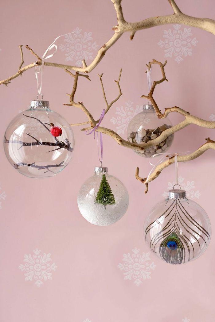 Glaskugeln füllen mit verschiedenen Elementen, Pfauenfeder und Holzstäbchen, kleines rotes Vögelchen und Weihnachtsbaum