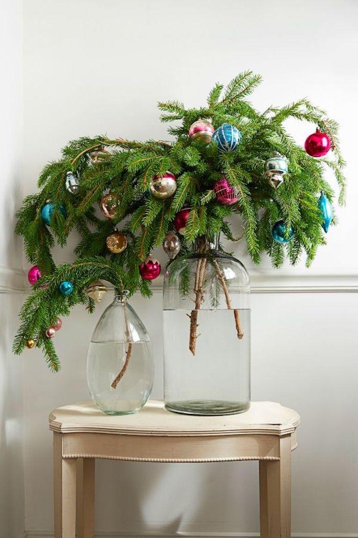 Tannenzweige in Glasvasen, geschmückte mit bunten vintage Christbaumkugeln