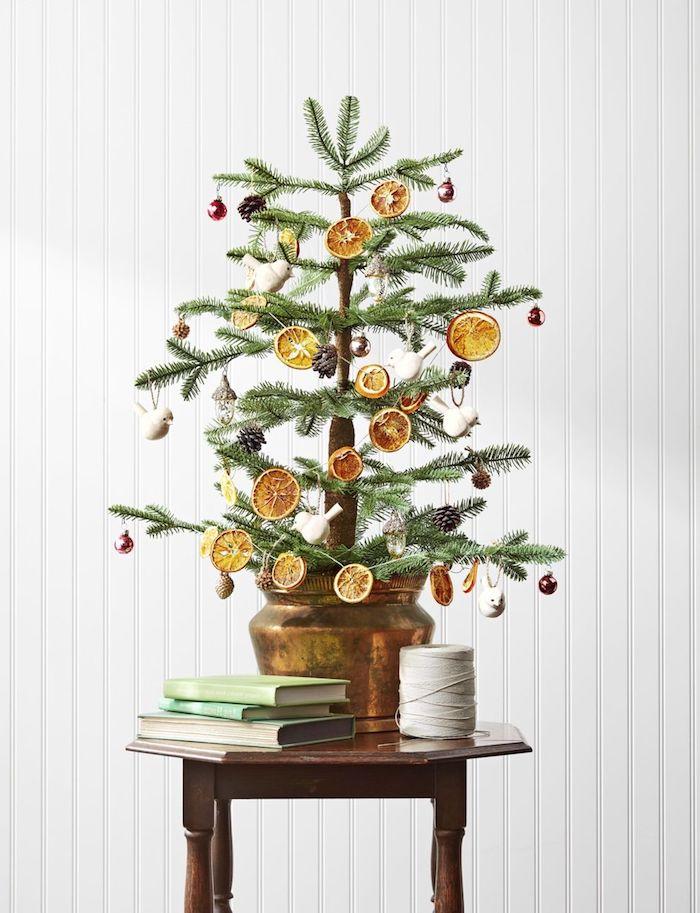 Kleiner echter Weihnachtsbaum in Blumentopf, geschmückt mit getrockneten Orangenscheiben, Tannenzapfen und Kugeln