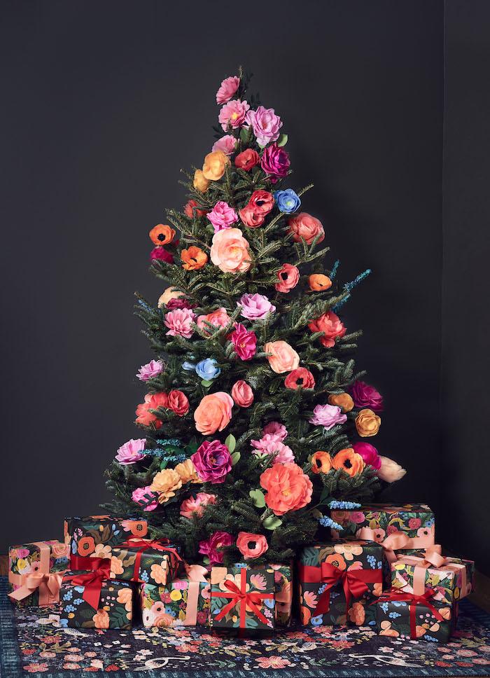 Künstlicher Weihnachtsbaum geschmückt mit bunten Blumen, Geschenkverpackungen mit Blumenmotiven