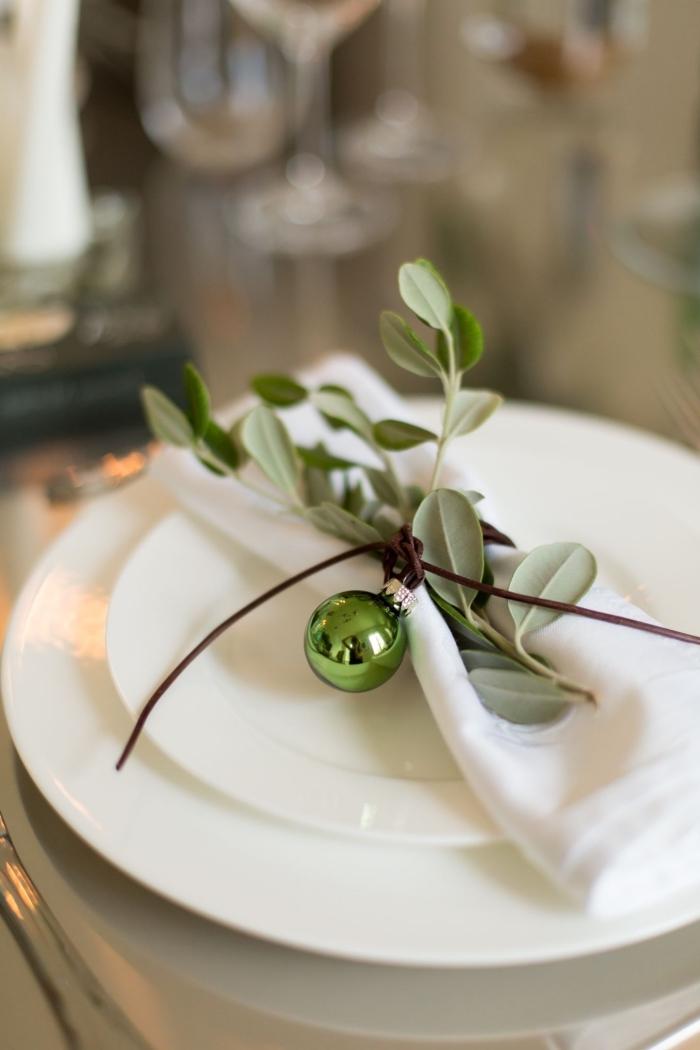 weihnacchtsdeko tisch, weiße teller, grüne zweige, tellerdeko zu weihnachten, kleine weihanchtkugel