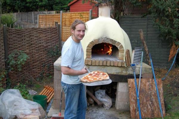 pizzaofen im garten - ein mann macht pizza