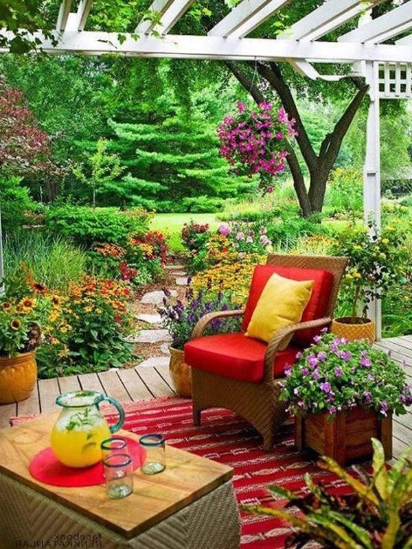 sitzgelegenheit-im-garten-mit-farbigem-deko-und-farbenforhe-pflanzung
