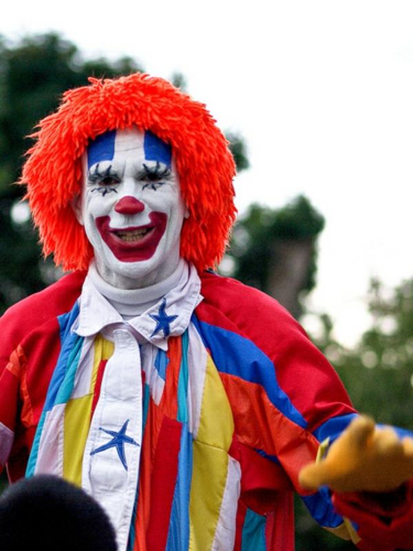 clownschminken - lustiges aussehen eines mannes - mit einer orange perücke