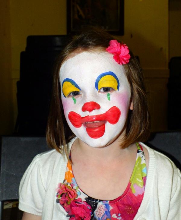 clownschminken - ein mädchen sieht lustig aus - mit einer blume in den haaren