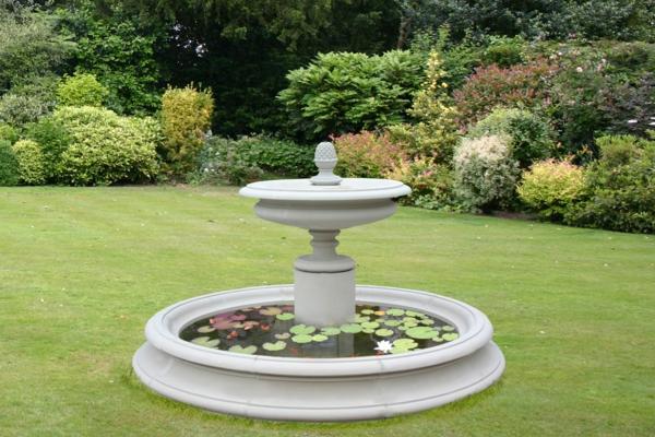 springbrunnen in weißer farbe - auf dem gras