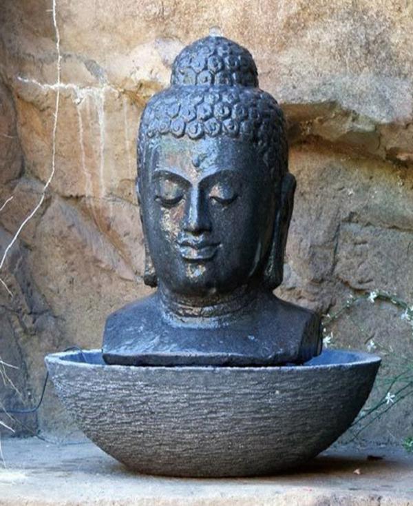 Buddha-Brunnen-eine-steinwand-dahinter