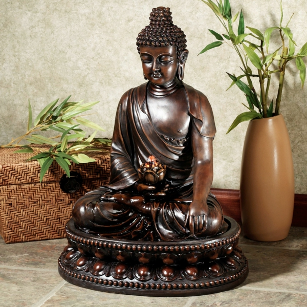 Buddha-Brunnen-eine-vase-mit-einer-grünen-pflanze-daneben