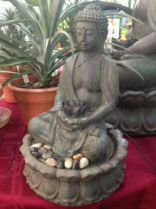 Buddha-Brunnen-neben-einer-topfpflanze