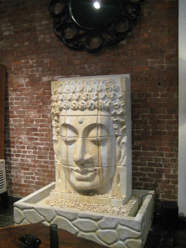 Buddha-Brunnen-vor-einer-ziegelwand
