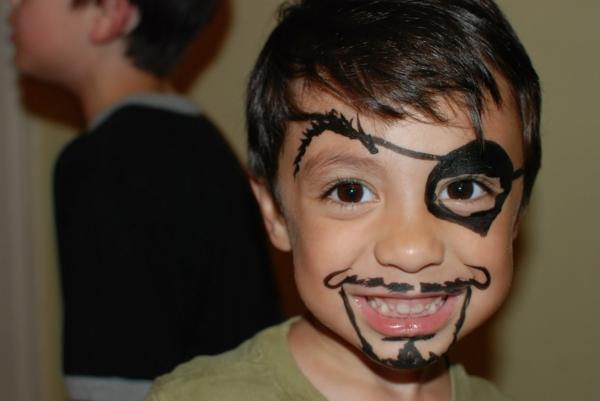 kleiner lächelnder junge mit piratschminken