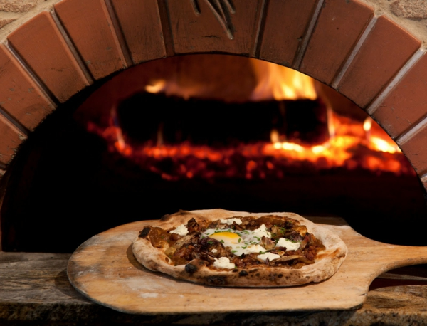 schöner pizzaofen und eine pizza davor