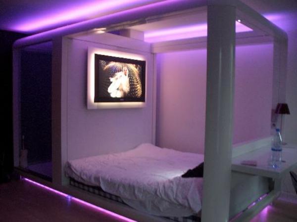 kleines schlafzimmer mit einer lila beleuchtung