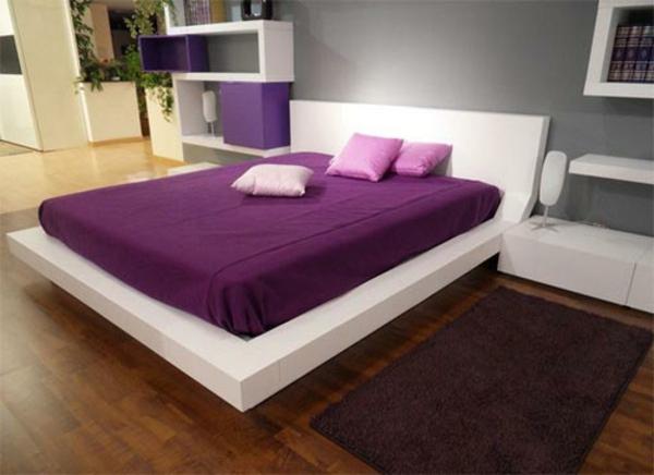 schlafzimmer mit einem schönen bett mit lila bezügen