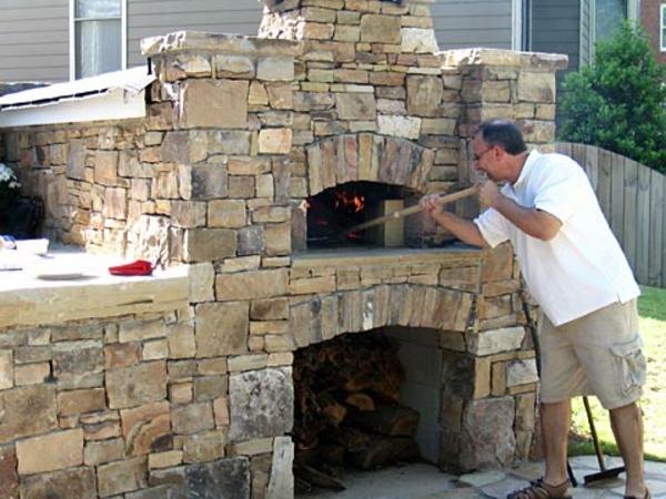 ein mann im garten, neben dem pizzaofen