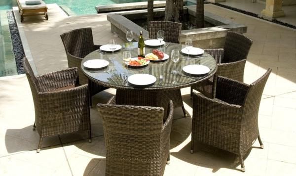 moderner garten mit einem runden tisch und stühlen aus rattan