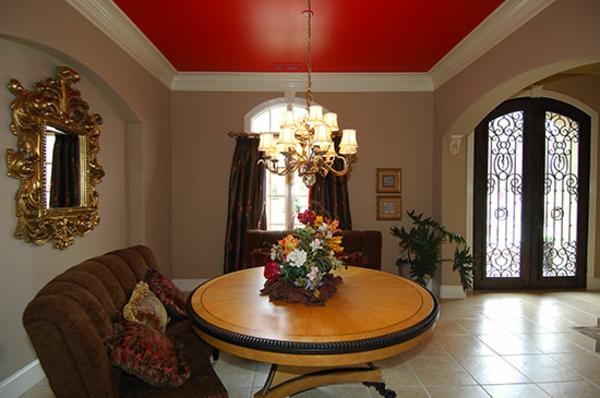 runder holztisch im wohnzimmer mit einer roten zimmerdecke