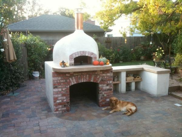 hund liegt neben einem pizzaofen aus stein und ziegeln im garten