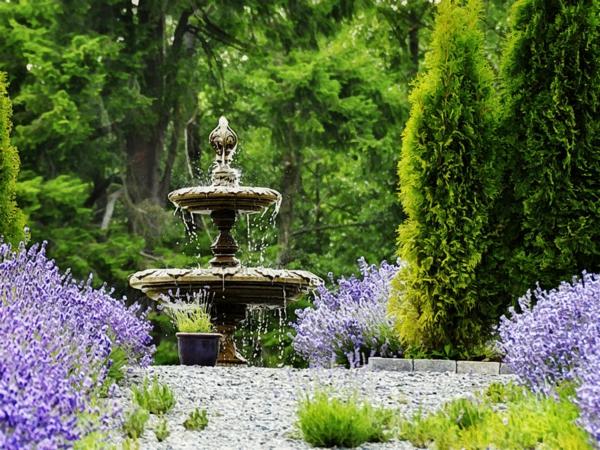 grüner schöner garten mit einem coolen springbrunnen