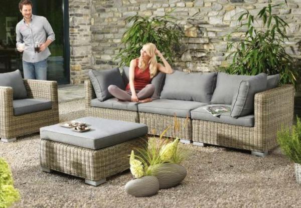 garten-loungemöbel-eine-frau-sitzt-auf-einem-rattansofa