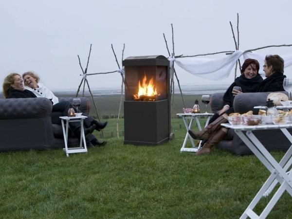 moderner garten mit einem kamin und leuten, die sich entspannen