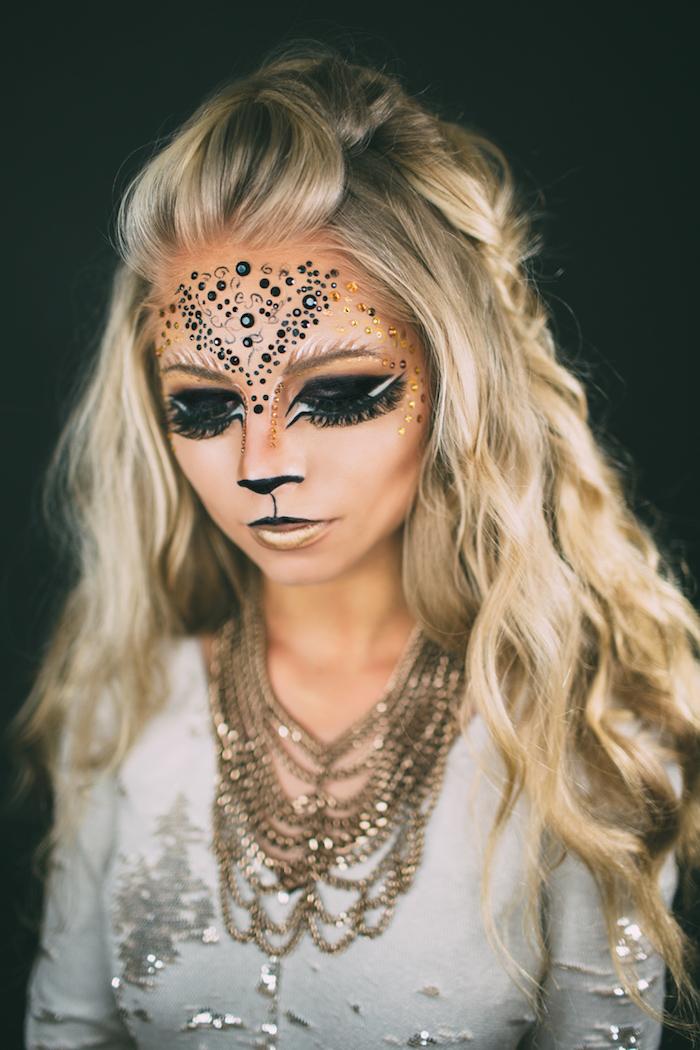 Katze schminken für Halloween, schwarze und orangefarbene Kristalle auf der Stirn, schwarzer Lidschatten, goldener Lippenstift