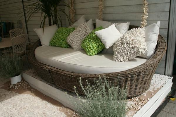viele dekokissen auf einem rattan-sofa im garten