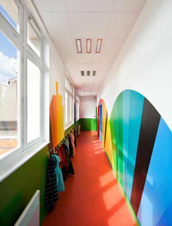kindergarten-mit-regenbogen-motiven-sehr-interessanter-flur-mit-bunter-wandgestaltung-großen-fenstern-und-kleiderehändern