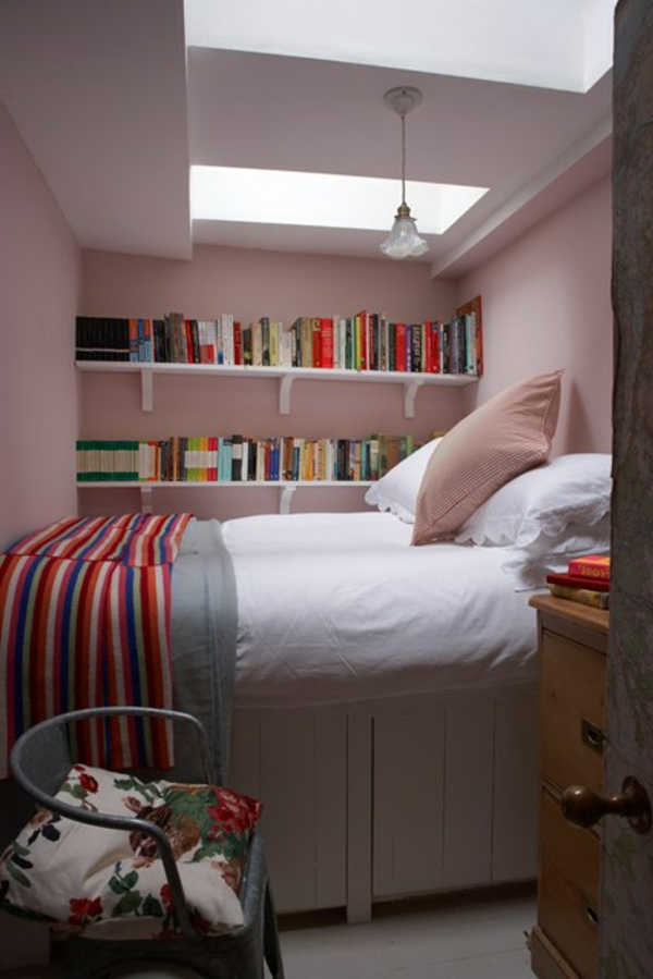 weiße bücherregale und weißes bett im kleinen schlafzimmer