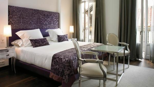 schlafzimmer mit einem lila bett und zwei stühlen