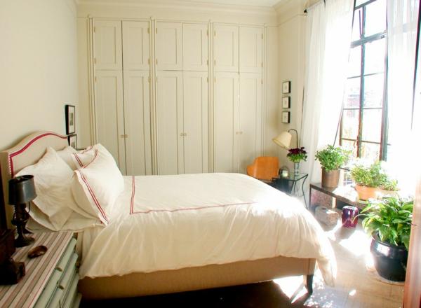 pflanzen-im-schlafzimmer-neben-einem-bequemen-weißen-bett