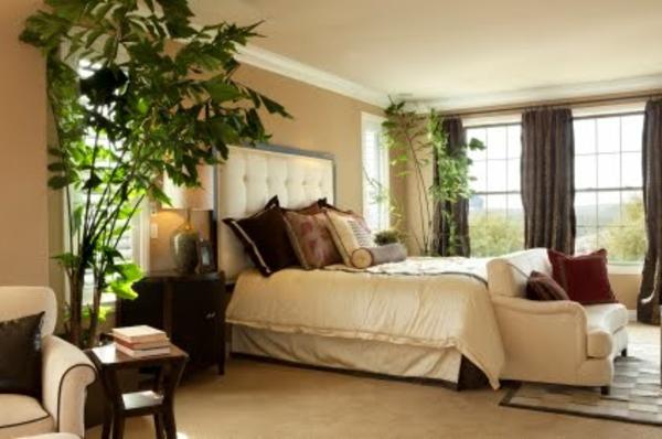pflanzen-im-schlafzimmer-neben-einem-weißen-bett-mit-dekorativen-kissen