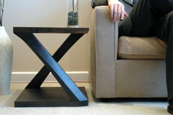 schöner-kleiner-tisch-mit-sich-durchkreuzenden-beinen-neben-einem-sofa