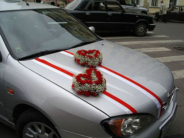 autoschmuck zur hochzeit - herzen aus blumen mit roten akzenten
