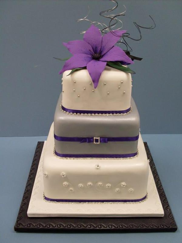 weiße-mehrstöckige-torte-zur-hochzeit-mit-einer-lila-blume