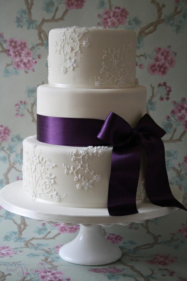 weiße-mehrstöckige-torte-zur-hochzeit-mit-einer-lila-schleife