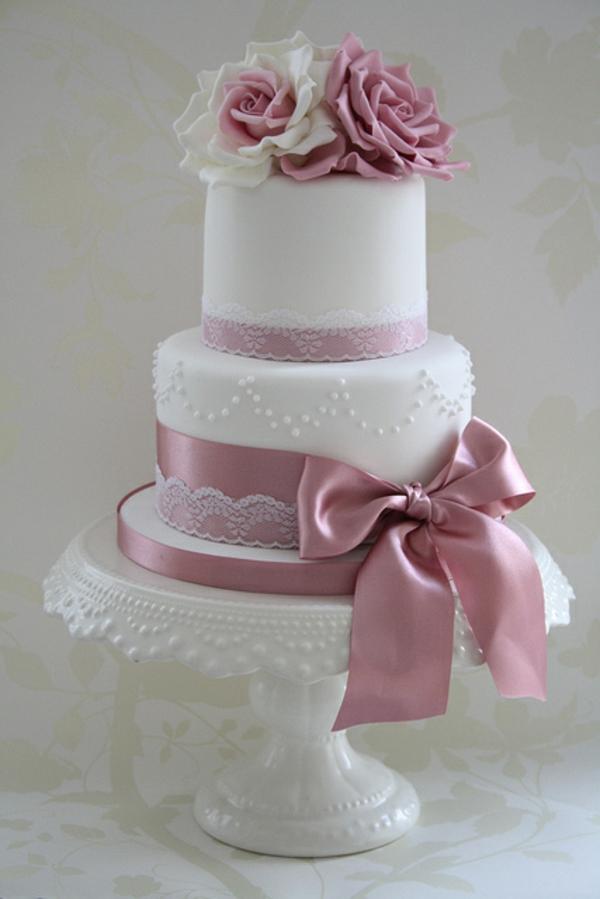 weiße-mehrstöckige-torte-zur-hochzeit-mit-einer-rosigen-schleife