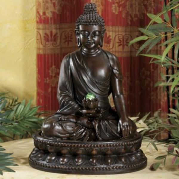 wunderschöner-Buddha-Brunnen-neben-einer-grünen-pflanze