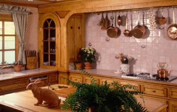 landhaus dekoration - küche mit hängenden pfannen an der wand und einer hase-skulptur