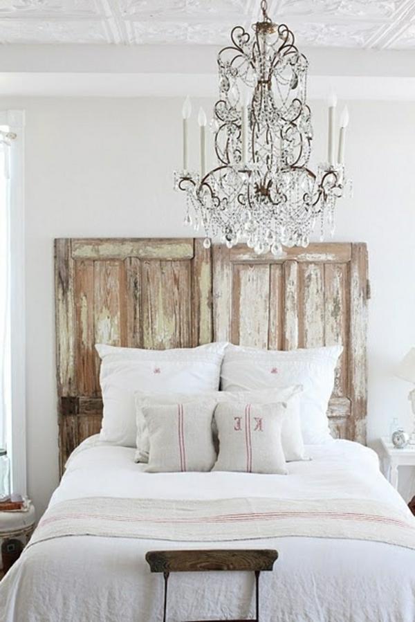 schlafzimmer imlandhausstil - auffälliges kopfbrett aus holz und kristallleuchter