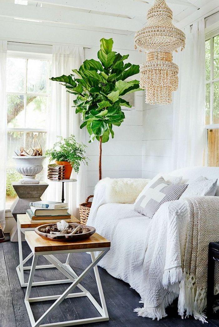 Wohnzimmer einrichten, weißer Sessel, viereckiger Couchtisch, verspielter Kronleuchter und große Grünpflanze