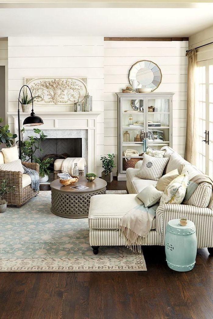 Wohnzimmer Einrichtung in Rustic Wohnstil, Wandfarbe Weiß, runder Couchtisch aus Metall und Holz, Rattansessel und weißes Sofa, schwarze Stehlampe